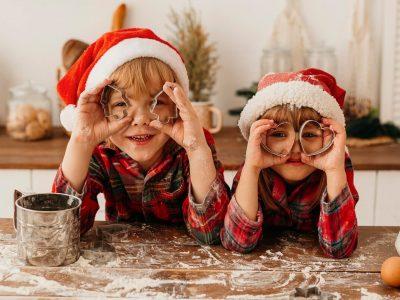 Duas Crianças Com Gorro De Papai Noel Brincando Com Formas De Biscoito