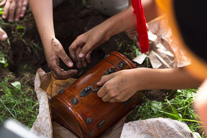 Mãos de crianças sujas de terra enquanto pegam um tesouro