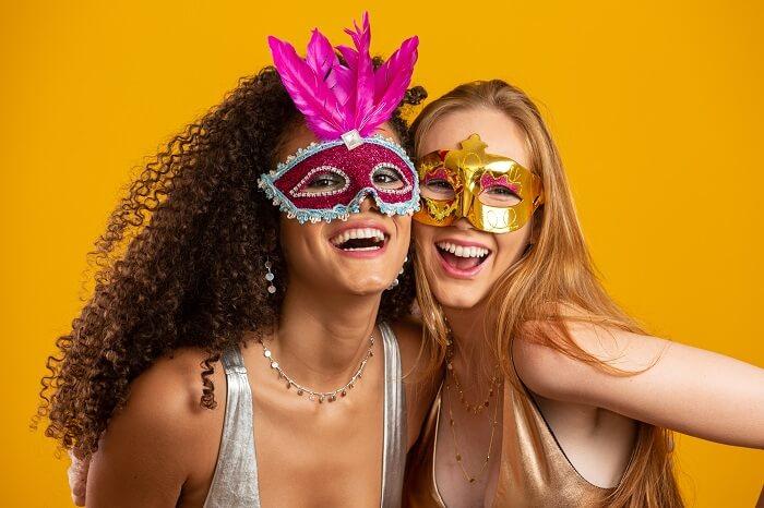 Duas amigas sorrindo com máscaras de carnaval
