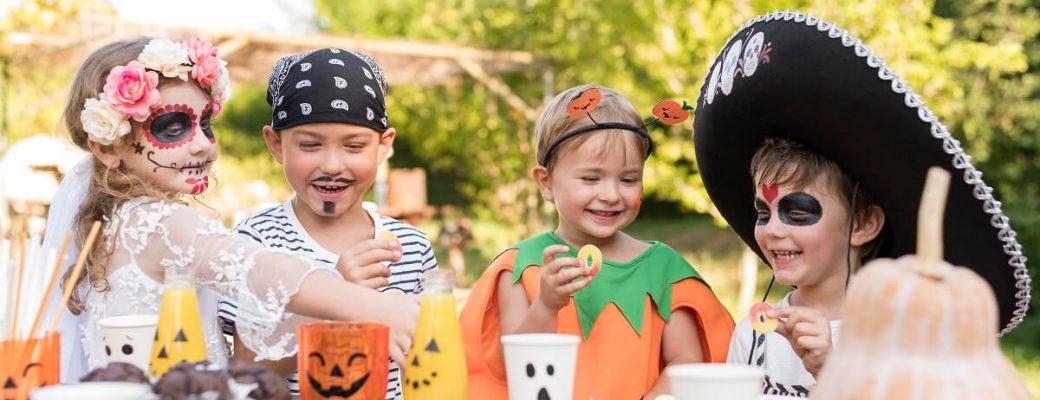 Quatro Crianças Fantasiadas Sentadas Ao Redor De Uma Mesa Em Um Jardim