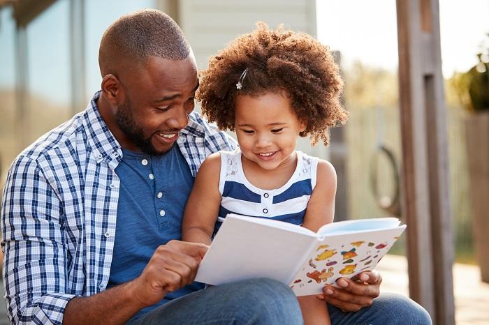 Pai negro lê livro para filha
