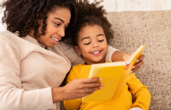 Menina e mãe negras lendo livro