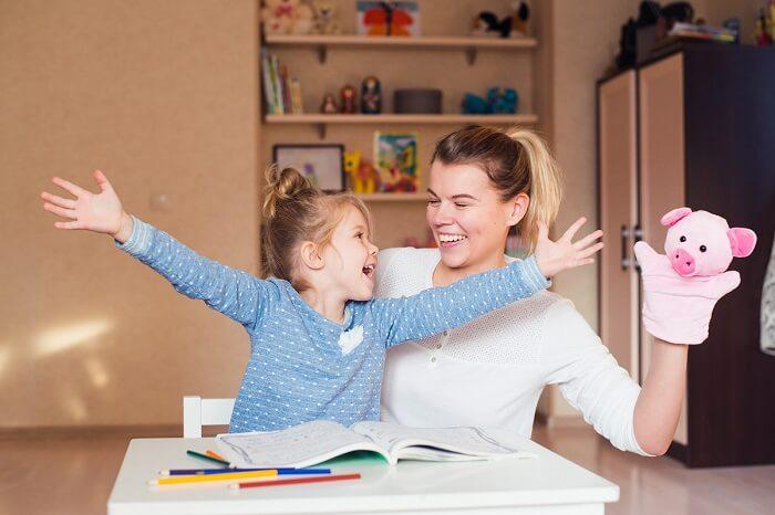 Mãe e filha brincando com boneco de fantoche
