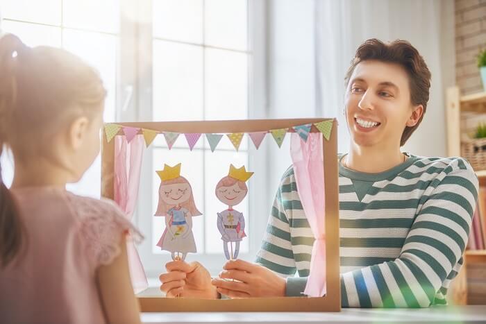 Pai e filha brincando com boneco de fantoche de papel